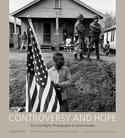 "Cover of the book ""Controversy and Hope"" showing a photograph of a young African-American man carrying the American flag while white soldiers and African-American children look on. Photograph was taken during the 1965 Selma to Montgomery March for Voting Rights."